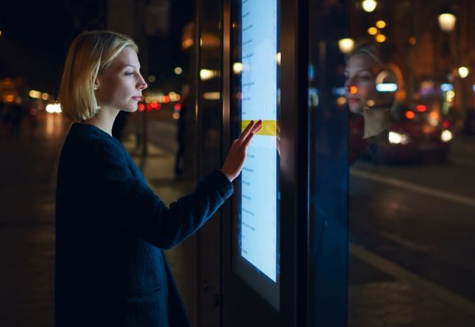 Woman using a large outdoor touch screen