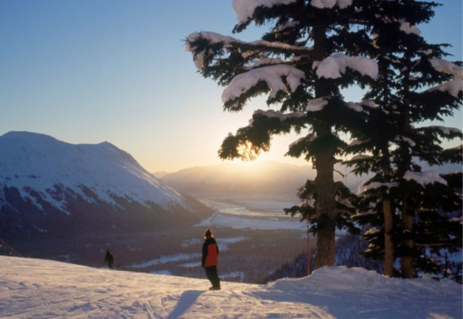 woman standing on a snow mountain facing the sunrise