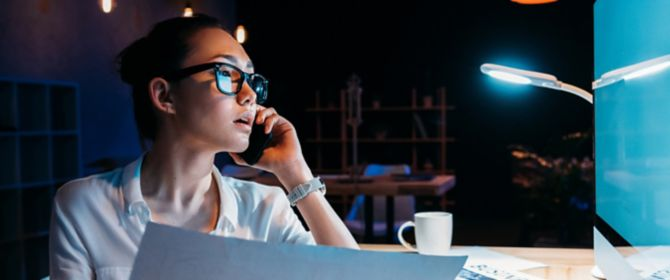 Woman talking on the phone and looking at her computer while working