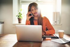 Woman talking on phone working on laptop at desk