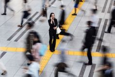 Woman talking over phone in crowd standing on yellow tiles