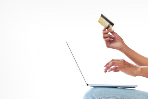 a woman using her credit card to make an online payment at home
