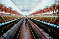 Woman watching red interiors of a textile manufacturing plant