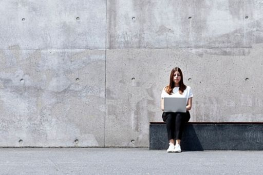 woman with laptop against a concrete wall