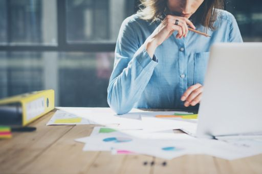 Woman working laptop papers on desk