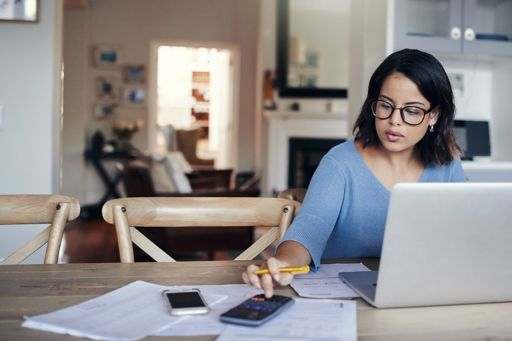 A woman using multiple digital devices at her kitchen table