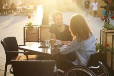 Women with special abilities sitting on a wheel chair while enjoying outside in a café with man and having coffee