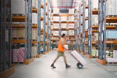 Worker pushing a hand truck in a warehouse