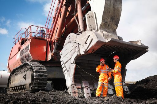 Workers standing with a large digger in a coal mine
