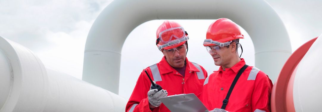 KPMG IFRS 15 (new revenue standard) for oil and gas publication image: workers standing next to oil and gas pipelines and equipment
