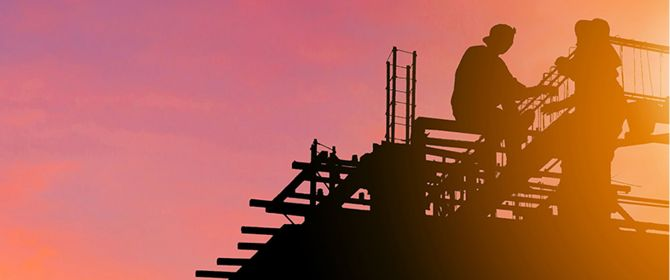Silhouette of workers working on a construction site at evening