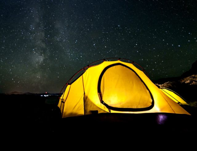 Yellow camping and hiking tent at night under shining stars