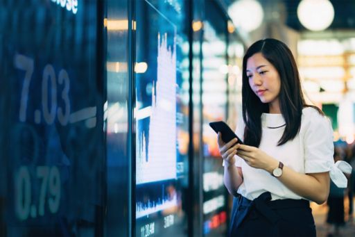 Young Asian businesswoman checking financial trading data on smartphone by the stock exchange market display