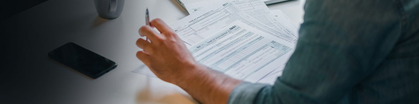 young businessman in office filling tax return documents