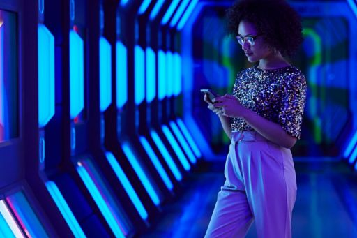 Young businesswoman looking at smartphone in futuristic corridor