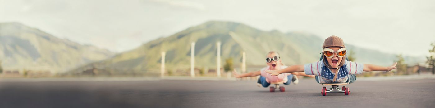 Young children on skateboards imagine they are flying