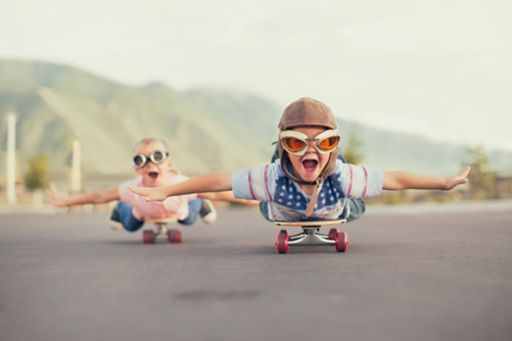 Young children on skateboards imagining that they are flying
