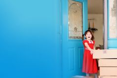 Young girl at front door with online delivery