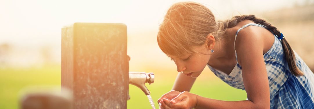 Young girl drinking water from tap with her hands