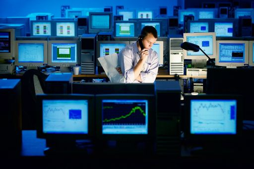Businessman talking on the phone surrounded by computers