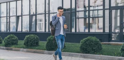 young man walking with phone in hand