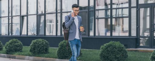 young man walking with phone in office park