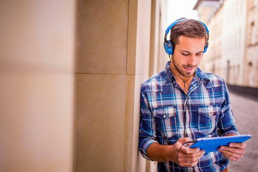 Young man with blue tablet and headphones