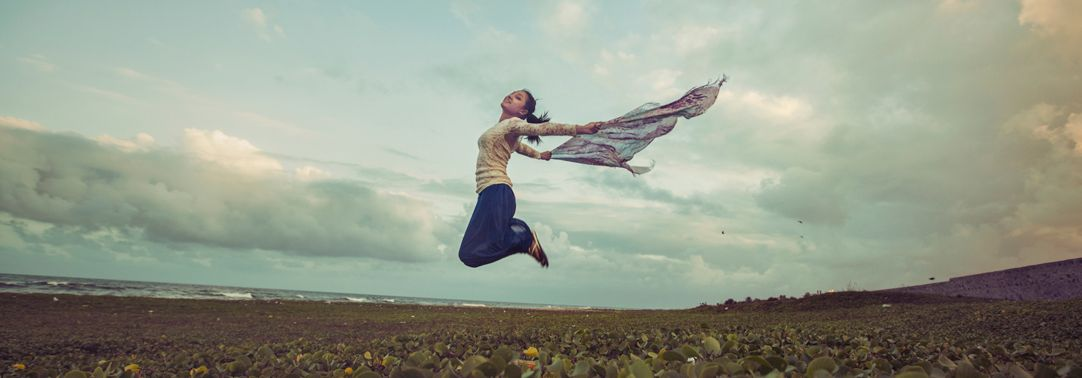 Young woman jumping with scarf in the wind