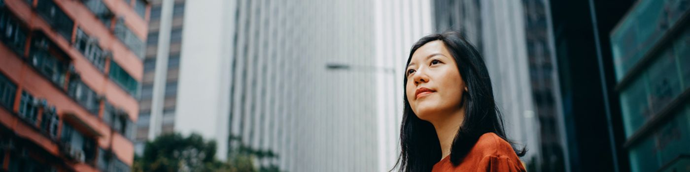A young woman stands among skyscrapers